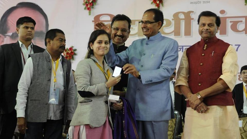 Madhya Pradesh chief minister Shivraj Singh Chouhan gifting a phone to a student.