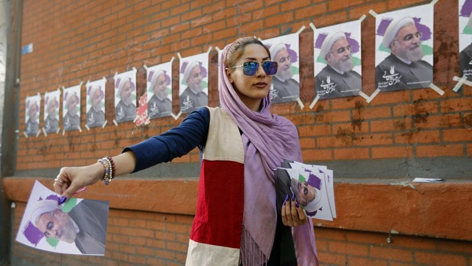 Supporters of Iranian President and election candidate Hassan Rouhani distribute brochures ahead of the Iranian presidential election in the streets of the capital Tehran on May 17, 2017.