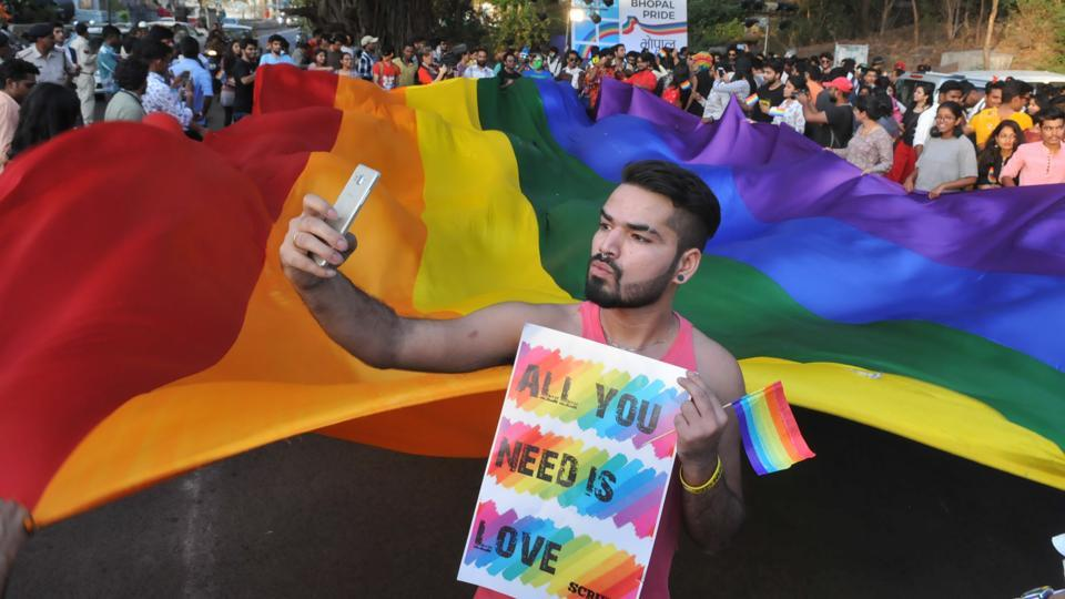 A supporter of the LGBT community takes a selfie with a rainbow flag to mark the International day against Homophobia and Transphobia in Bhopal.A government owned local train network in southern India recently employed 23 transgender women. In light of these changes hopes of the LGBT movement in India glitter against Section 377 of  Indian Penal Code which considers same sex marriage as 'unnatural offences' and a criminal act. (Mujeeb Faruqui/HT Photo)