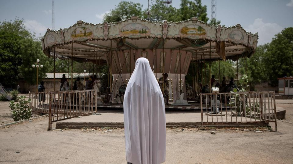 A girl watches other children playing on a merry-go-round in an abandoned amusement park in Maiduguri, Nigeria, on April 27, 2017. In Maiduguri, where the population has doubled to more than two million as a result of Boko Haram insurgency, thousands of children are homeless.