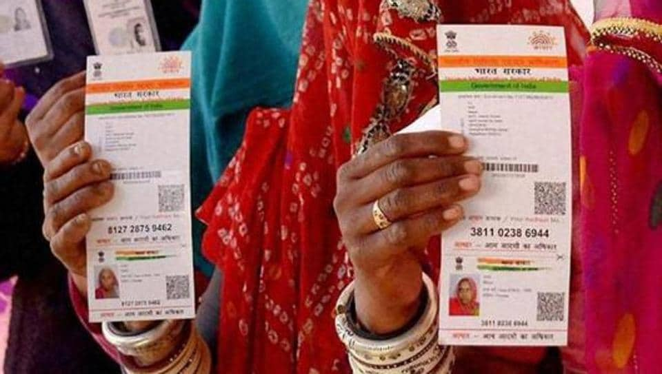 Rajasthani women showing their Aadhaar cards while standing in a queue to vote for Ajmer District Panchayat elections.