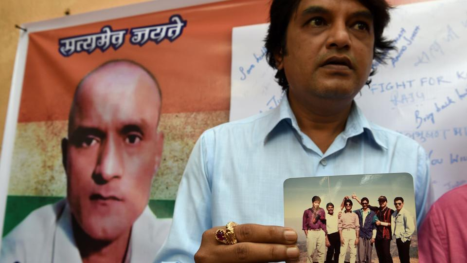 A man holds a photograph of Kulbhushan Jadhav after the International Court of Justice ordered Pakistan to stay the execution of the Indian national.