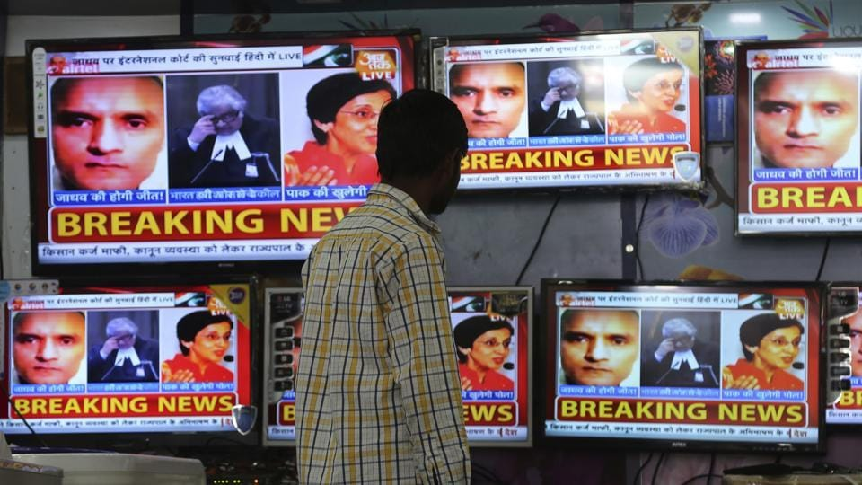 A boy watches as television channels that show news about International Court of Justice hearing the case of former Indian naval officer Kulbhushan Jadhav.