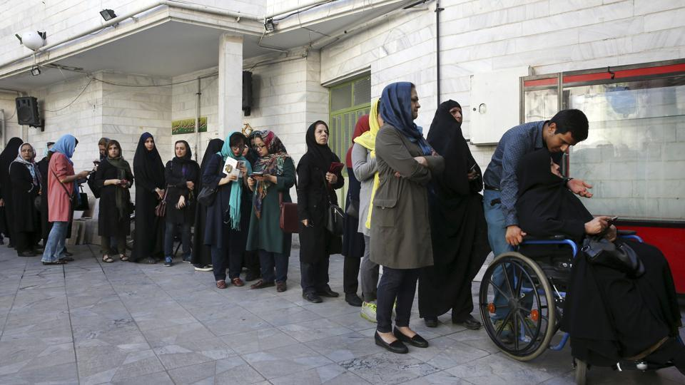Iranian voters queue at a polling station for the presidential and municipal council election in Tehran on Friday.