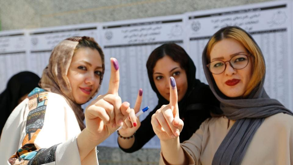 Iranians show their ink-stained fingers after casting their ballots for the presidential elections at a polling station in southern Tehran on May 19, 2017.