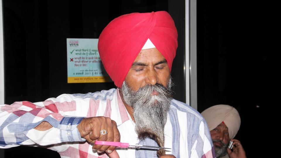 Bahona village sarpanch Harbhajan Singh cutting his beard outside the DC office in Moga on Friday, May 19.
