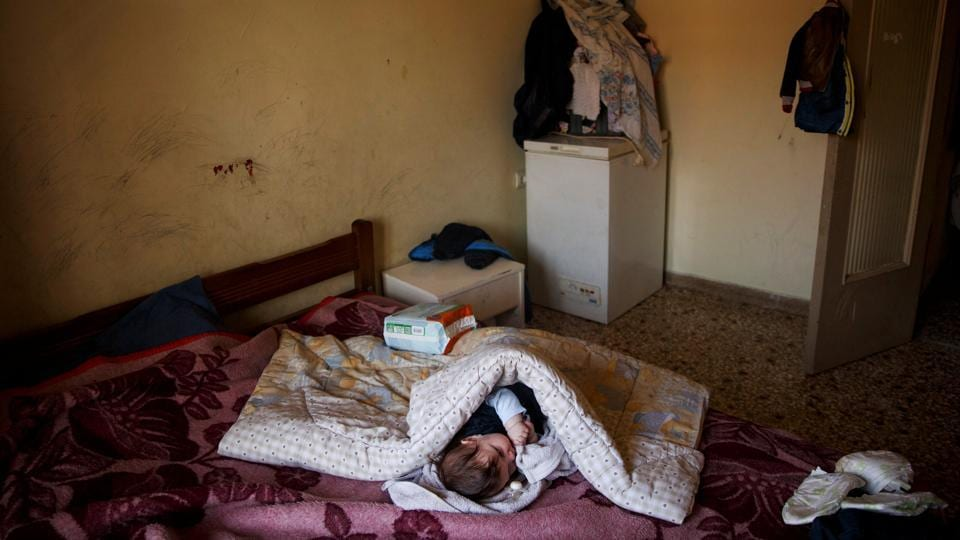 A baby rests in her parents bed at her house in Athens. Greece is on its way to its third international bailout since 2010. Struggling to contain a debt it is now in the brink of being disowned by the European Union. (Alkis Konstantinidis/REUTERS )