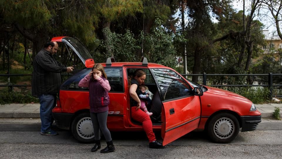 The Argyros family get into their car, which was donated, after receiving goods from  an NGO for big families in Athens.Five years since abandoning their home in Leros for Athens, they are trapped in a cycle of unemployment and debt. (Alkis Konstantinidis/REUTERS )