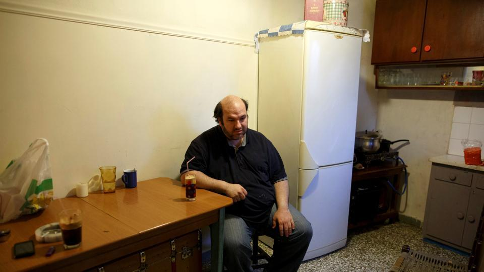 Kostas Argyros has his morning coffee at his home. He picks up occasional jobs here and there while his wife has been jobless for almost a decade now.  (Alkis Konstantinidis/REUTERS )