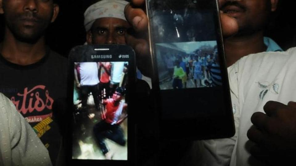 In the photo displayed on the phone, Mohammed Naeem is pleading to a group of villagers as blood trickles down from his head.