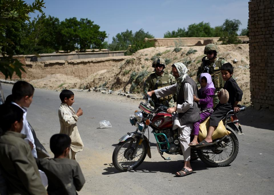 An Afghan motorcyclist turns his bike near the site of a roadside bomb blast at Abed Kheel near Charikar district of Parwan province.
