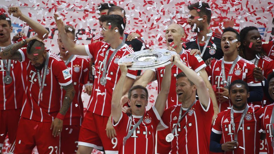 Bayern Munich's Philipp Lahm and Xabi Alonso celebrate with the trophy after winning the Bundesliga title.