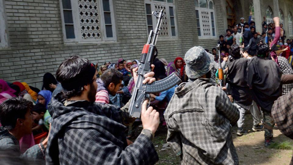 Suspected militants brandish their guns and shout slogans during the funeral of a slain comrade, killed in a shoot out with the police, at Qoimoh in Kulgam district of south Kashmir on May 7.