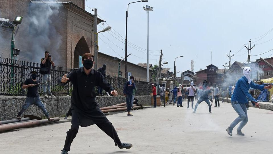"""Kashmiri protesters throw stones at security personnel outside the Jamia Masjid in Srinagar on Friday. The sting operation had shown JKNF leader Nayeem Khan saying that all """"separatists get funds from Pakistan""""."""