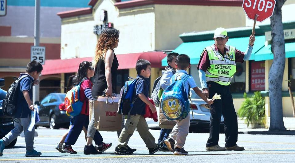 A school crossing guard stops traffic as children cross the road in Monterey Park, California on April 28.