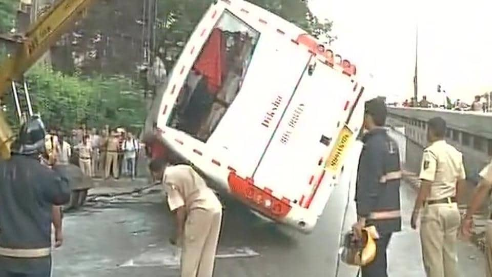 Workers lift the bus that hit a divider and overturned near Dadar TT junction in Dadar East on Sunday morning.