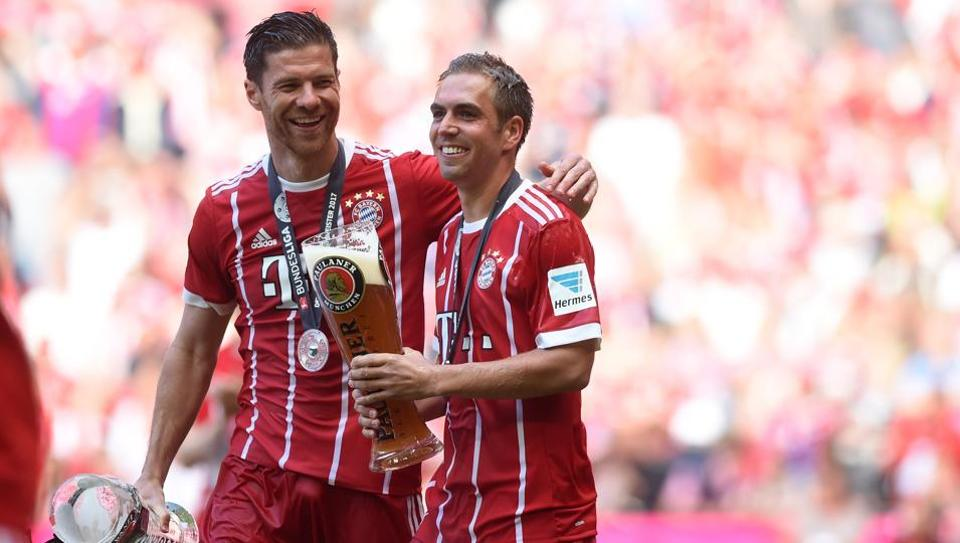 Bayern Munich players Philipp Lahm (R) and Xabi Alonso (L) celebrate with beer after their Bundesliga match against SC Freiburg in Munich.