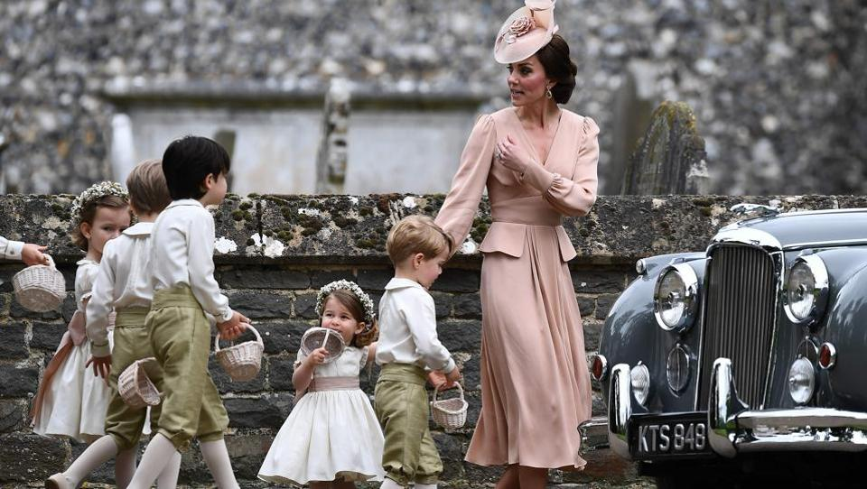 Britain's Catherine, Duchess of Cambridge (R) beckons the bridesmaids and pageboys, including Britain's prince George (2R) and Britain's princess Charlotte (3R) towards a waiting car . (Justin TALLIS / AFP)