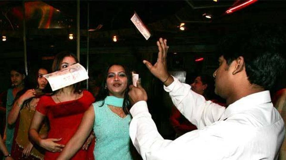 Money rains down on performers in bright red and blue dress in a Kolkata bar.