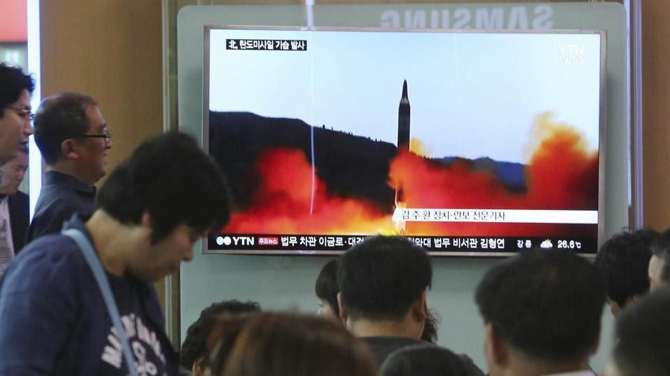 People watch a TV news program showing a file image of a missile launch by North Korea at the Seoul Railway Station in South Korea on Sunday.