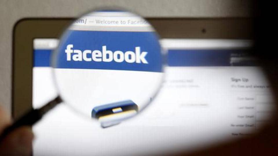 A Facebook logo on a computer screen is seen through a magnifying glass.