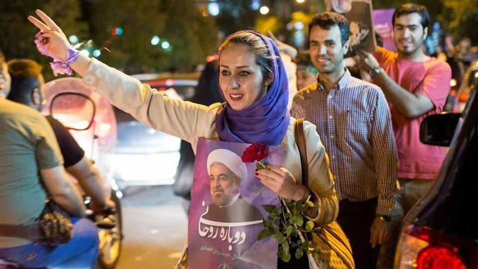 Woman holds a poster of Iranian President Hassan Rouhani during a campaign rally in Tehran, May 17, 2017