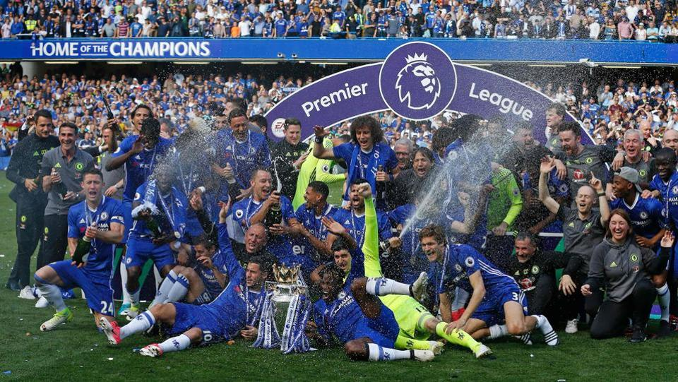 The champagne is sprayed as Chelsea's players gather on the pitch with the Premier League trophy. (AFP)