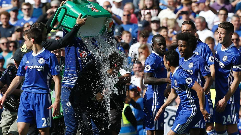 Chelsea's Italian head coach Antonio Conte is soaked with water, as players continue their celebrations. (AFP)