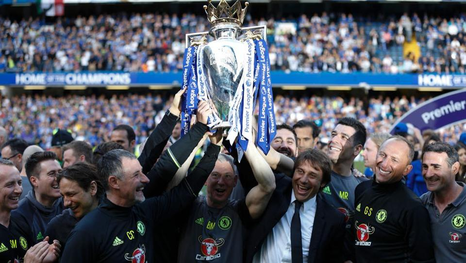 Antonio Conte holds aloft the trophy along with his support staff. (AFP)