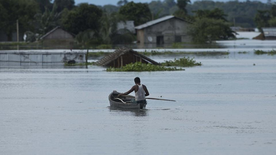 A man moves on a boat near submerged houses near Kaziranga national park in Assam in July  2016.