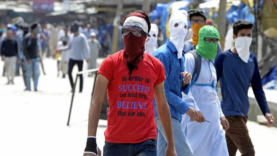 Kashmiri protesters look towards security forces during clashes after the Friday prayers in Srinagar, May 19, 2017
