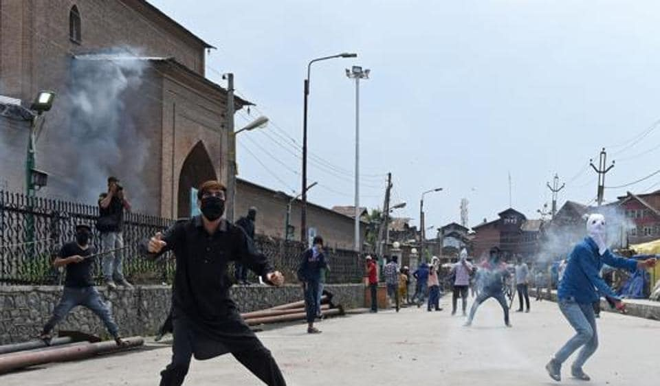 Kashmiri protestors throw stones towards Indian government forces during clashes outside Jamia Masjid in Srinagar. Top foreign investors in India have flagged the Kashmir unrest as risk to their investments in the country.