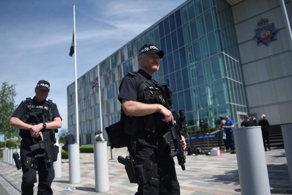 Flags fly at half-mast as armed British Police officers walk on patrol with their weapons outside of Greater Manchester Police force's headquarters in Manchester, during a visit by Britain's Prime Minister Theresa May.  (Oli SCARFF/AFP Photo)