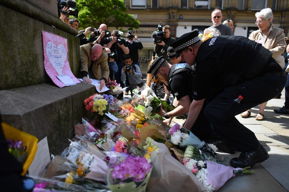 Police officers relocate floral tributes in St Ann's Square in Manchester, northwest England, laid as a mark of respect to those in killed and injured at the Manchester Arena.  (Ben STANSALL/AFP Photo)
