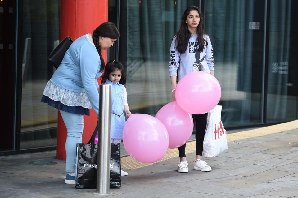 A woman (L) with two girls, one wearing a T-shirt of US singer Ariana Grande with balloons from the Ariana Grande concert at the Manchester Arena leave a hotel in Manchester, northwest England on May 23, 2017 following a deadly terror attack at the concert at the Manchester Arena the night before. Twenty two people have been killed and dozens injured in Britain's deadliest terror attack in over a decade after a suspected suicide bomber targeted fans leaving a concert of US singer Ariana Grande in Manchester.