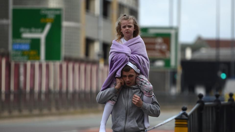A man carries a young girl on his shoulders near Victoria station in Manchester, northwest England on May 23, 2017. Twenty two people have been killed and dozens injured in Britain's deadliest terror attack in over a decade after a suspected suicide bomber targeted fans leaving a concert of US singer Ariana Grande in Manchester.