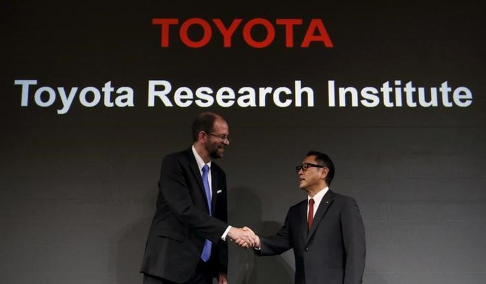 Toyota Motor Corp president Akio Toyoda (R) shakes hands with its executive technical advisor and CEO of its new company Toyota Research Institute Gill Pratt during a news conference in Tokyo on November 6, 2015.