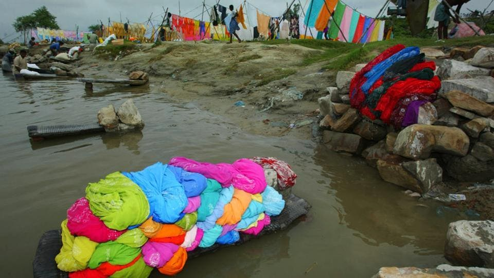 Piles of clothes lie on the banks of the Gomti River waiting to be washed, as washermen work nearby in Lucknow. Dhobi ghats still popular inspite of modern technology and the use of washing machines. (AP)