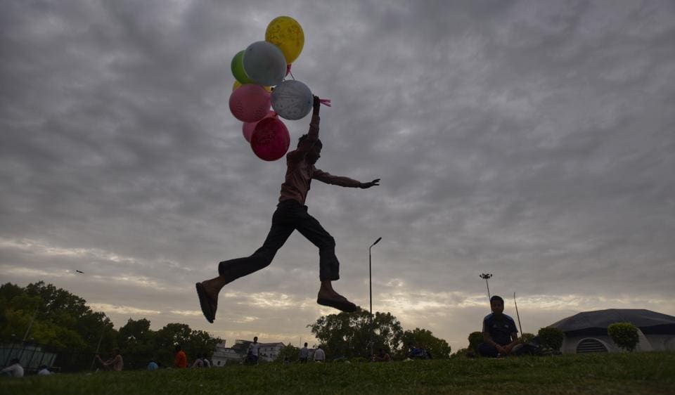 A balloon-seller enjoying Monday's cloudy weather at Connaught Place in central Delhi.