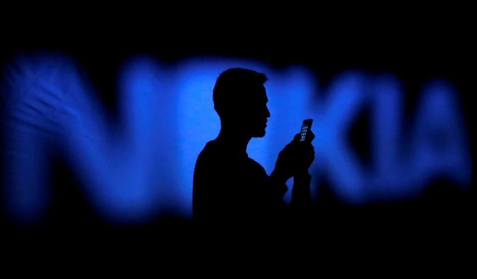A photo illustration of a man silhouetted against a Nokia logo in the central Bosnian town of Zenica.