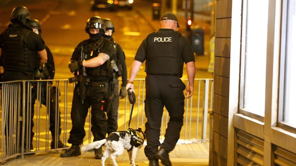 Armed police officers stand near the Manchester Arena, where US singer Ariana Grande had been performing, in Manchester, in northern England on May 23.