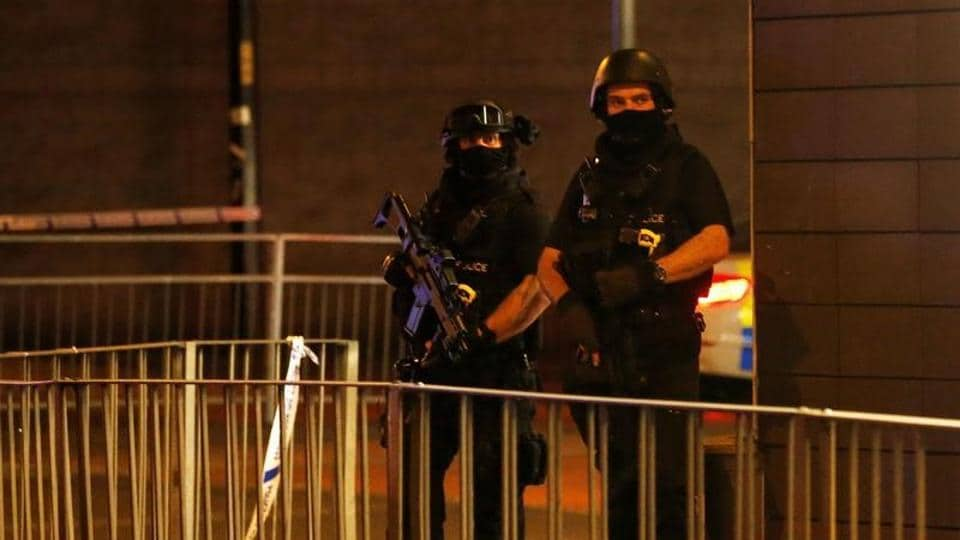 Armed police officers stand next to a police cordon outside the Manchester Arena, where US singer Ariana Grande had been performing, in Manchester, northern England, Britain.