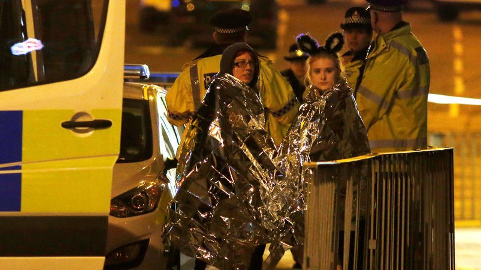 Two women wrapped in thermal blankets stand near the Manchester Arena, where U.S. singer Ariana Grande had been performing, in Manchester, northern England, Britain, May 23, 2017.