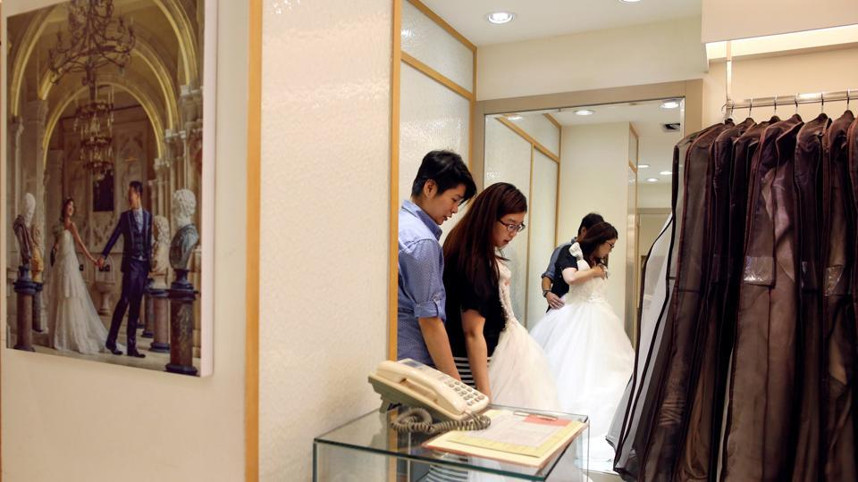 Daphne Chiang (R), an insurance consultant, tries on a wedding dress with her same-sex partner Kenny Jhuang in Taiwan. Currently Taiwan's Civil Code stipulates an agreement to marry can only be made between a man and a woman. (Tyrone Siu/REUTERS )