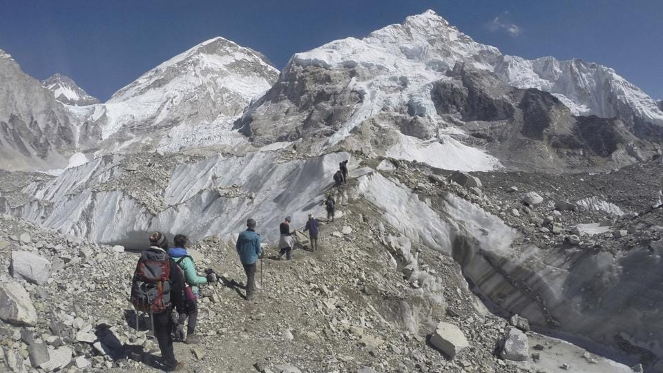 Trekkers pass through a glacier at the Mount Everest base camp. Thousands of tourists visit the base camp every year resulting in overcrowding and environmental degradation. (AP)