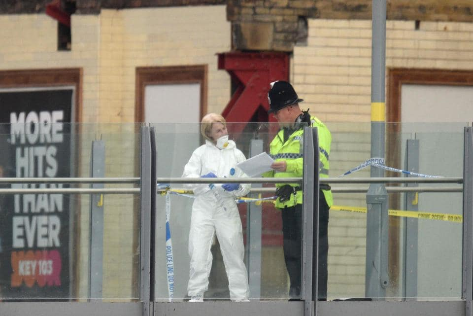 A forensic officer (L) collects evidence on a walkway between Victoria station and Manchester Arena following a deadly terror attack . (Oli SCARFF / AFP Photo)