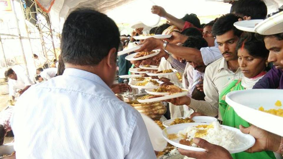 A teacher serves food at the mass wedding in Singrauli on Monday.