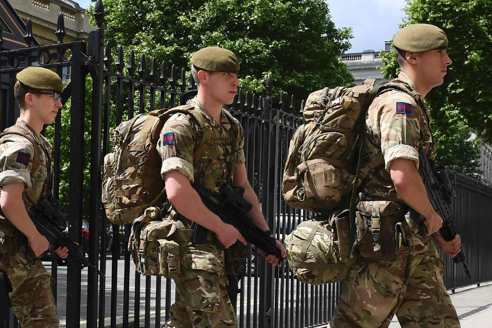 British soldiers enter a defence ministry building near the New Scotland Yard headquarters in London.