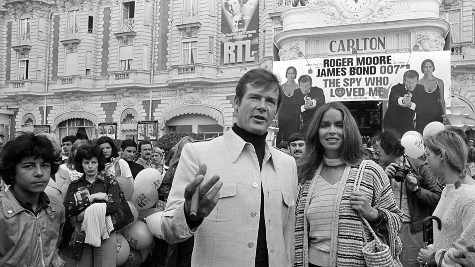 FILE - Actor Roger Moore, alias British secret agent James Bond, is accompanied by co-star Barbara Bach as they arrive for the screening of their latest 007 feature on May 20, 1977.  (AP)