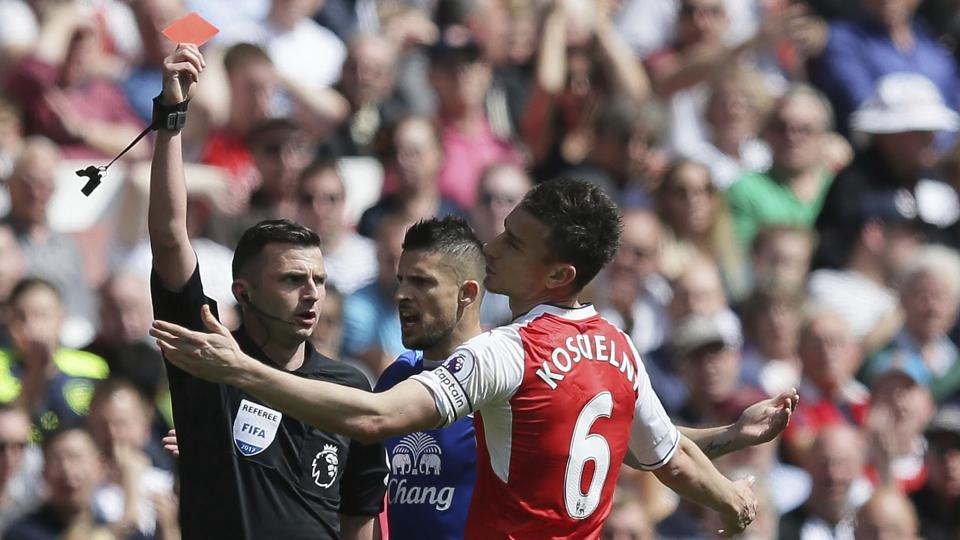 Arsenal's Laurent Koscielny (R) reacts to being shown the red card by referee Michael Oliver during the final game of the season against Everton.